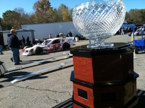 Doug Coby drives by the Whelen Modified Tour championship trophy in the pits at Thompson Speedway  the day before he won it