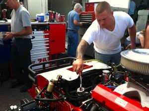Jimmy Blewett works on his Whelen Modified Tour car in the pits at New Hampshire Motor Speedway in July